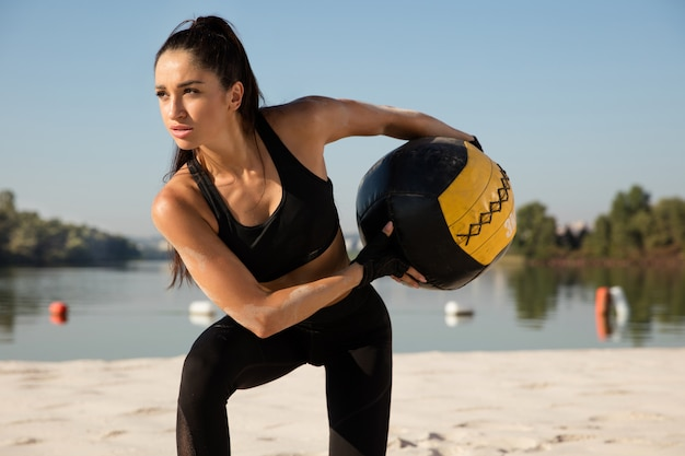 Молодая здоровая женщина делает выпады с мячом на пляже.
