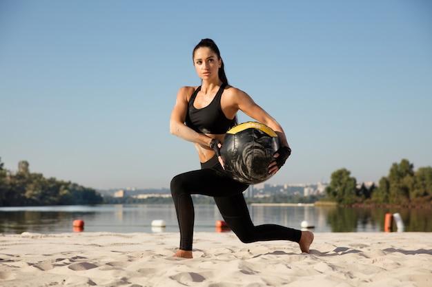 해변에서 공을 들죠 하 고 젊은 건강 한 여자.