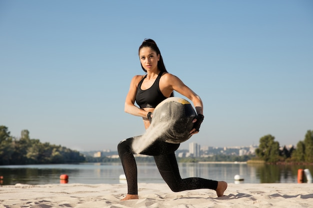 Young healthy woman doing lunges with ball at the beach