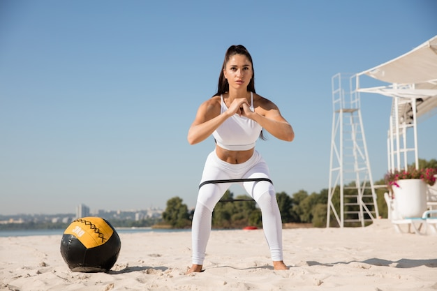 Young healthy woman doing squats with the ball at the beach.