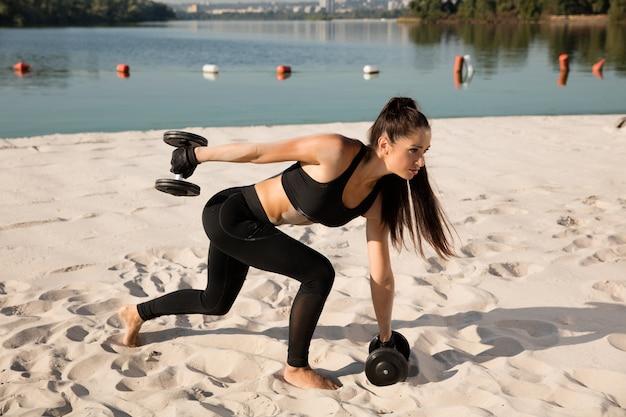 해변에서 무게와 스쿼트를하고 젊은 건강한 여자