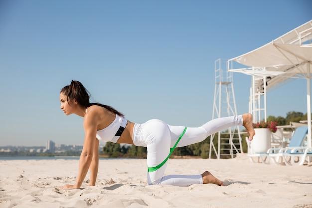 Молодая здоровая женщина делает упражнения на растяжку на пляже.