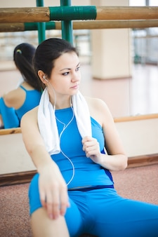 Young healthy woman drinking water in fitness