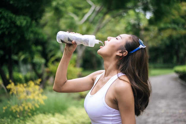 Young healthy woman drinking water from plastic bottles after jogging.