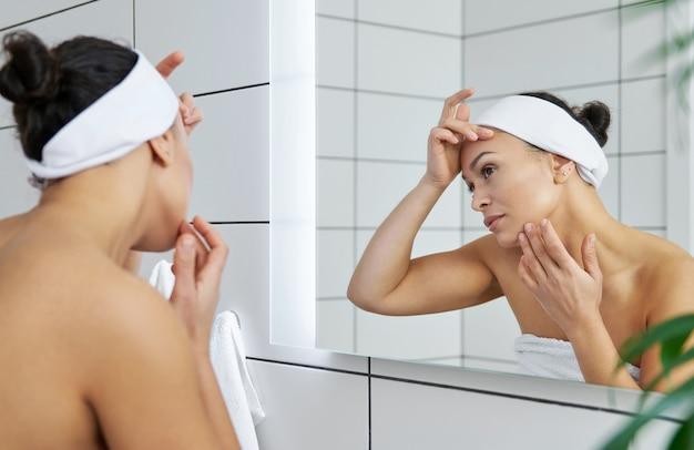 おびえた若い健康な女性は鏡の最初のしわを見ました