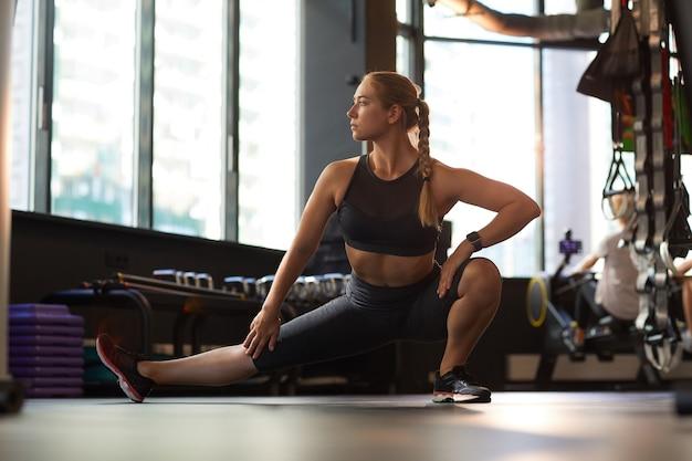 Молодая здоровая женщина в спортивной одежде разогревается во время тренировки в тренажерном зале