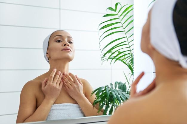 若い健康な女性は、バスルームの鏡の前で首をマッサージします