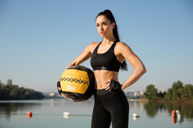 Молодая здоровая женщина позирует уверенно с мячом на пляже.