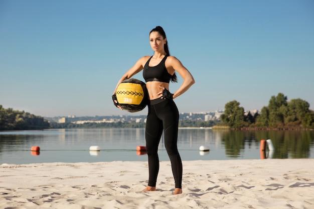 해변에서 공을 자신감 포즈 젊은 건강 한 여자