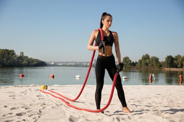 해변에서 로프와 함께 포즈 젊은 건강 한 여자.