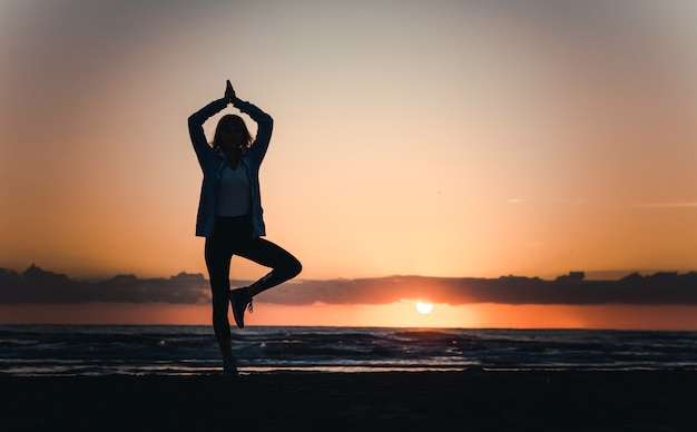 Young healthy woman practicing yoga on the beach