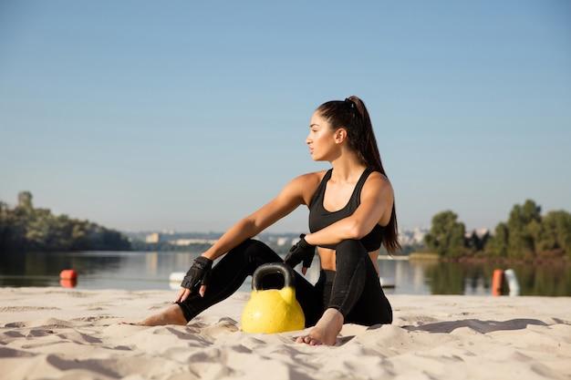 해변에서 연습 후 휴식하는 젊은 건강 한 여자.