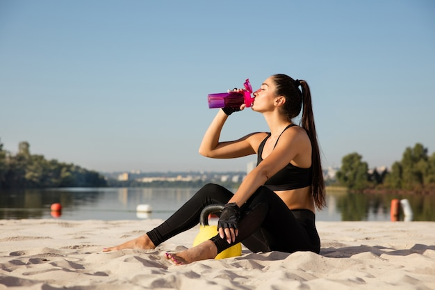 해변에서 연습 후 휴식하는 젊은 건강 한 여자