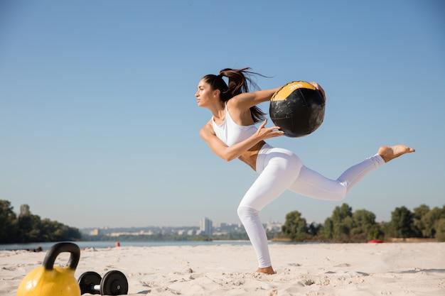 Молодая здоровая женщина работает с мячом на пляже.