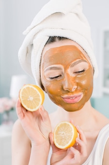 Young healthy woman in spa making treatments and face mud mask.