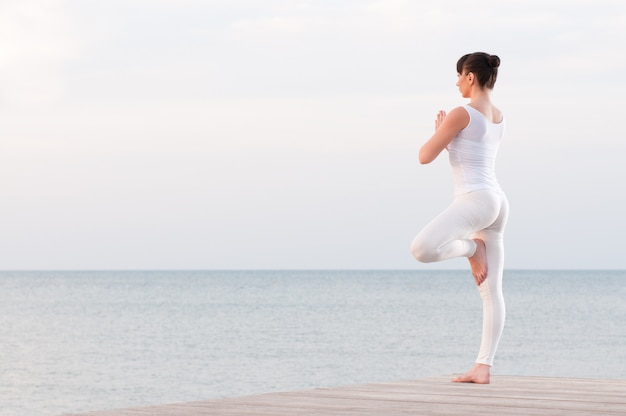 Young healthy woman standing on one leg while meditating and praying outdoor at sea