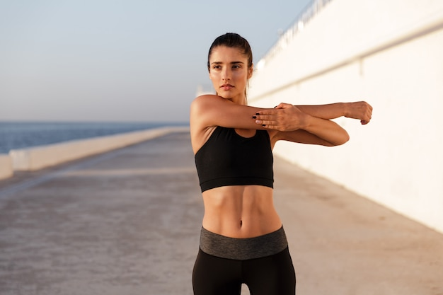 Young healthy woman stretching and training near sea