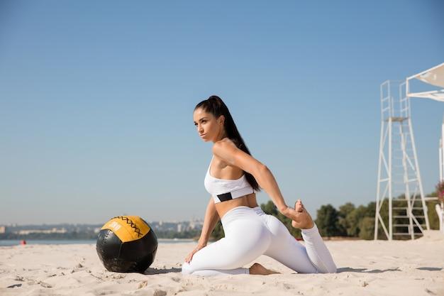 Молодая здоровая женщина растяжения с мячом на пляже.