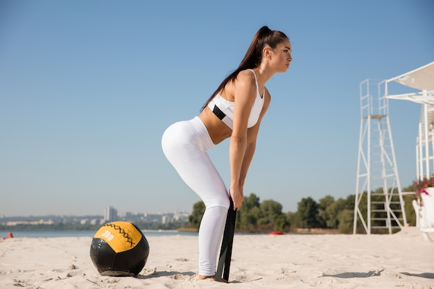 해변에서 공을 스트레칭 젊은 건강 한 여자.