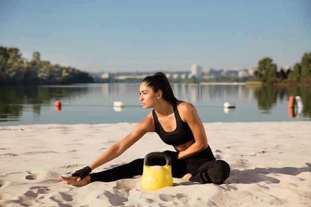 Молодая здоровая женщина растяжения с весами на пляже.