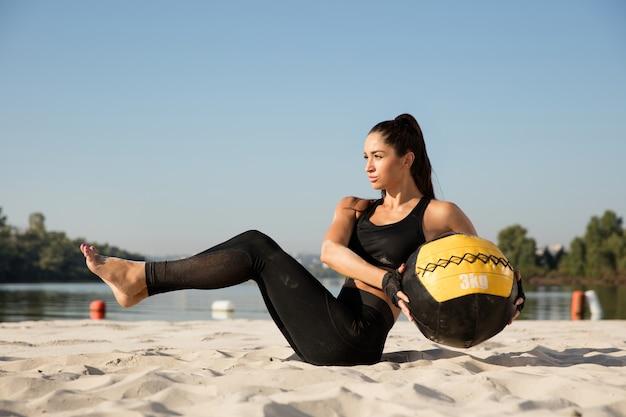 해변에서 공을 젊은 건강 한 여자 훈련 상체.