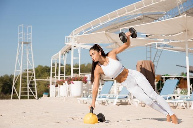 ビーチでウェイトトレーニングをしている若い健康な女性。