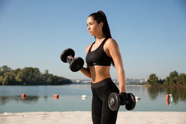 Молодая здоровая женщина тренировки верхней части тела с весами на пляже.