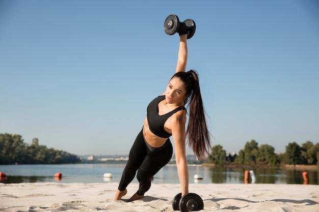 해변에서 무게와 젊은 건강한 여자 훈련 상체