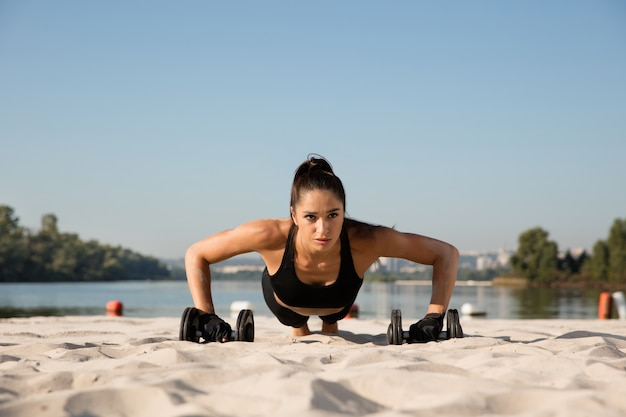 Young healthy woman training upper body with weights at the beach.