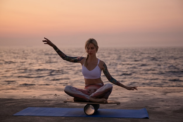 Young healthy woman with casual hairstyle sitting on wooden desk and balancing with hands, looking concentrated and calm, posing over seasde view on early morning