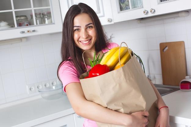 キッチンで新鮮な野菜を持つ若い健康な女性