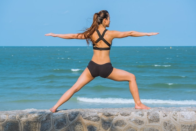 Young healthy yoga woman practicing yoga pose on beach in the morning