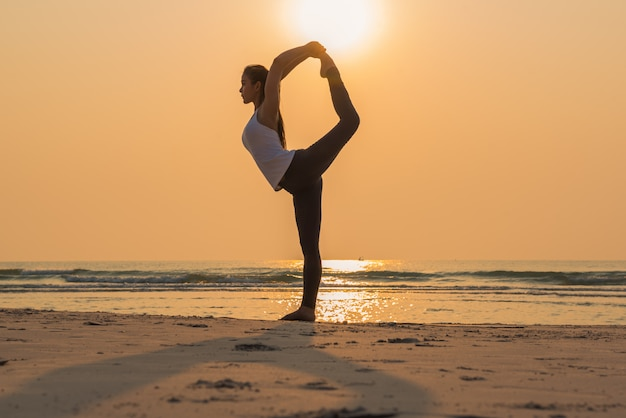 Young healthy yoga woman practicing yoga pose on the beach at sunrise
