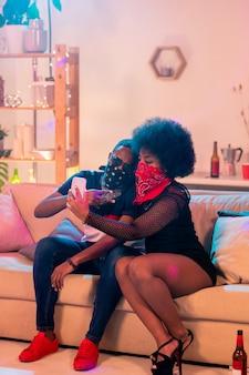 Молодая гетеросексуальная пара с банданами на лицах делает селфи, отдыхая на мягком диване в гостиной дома