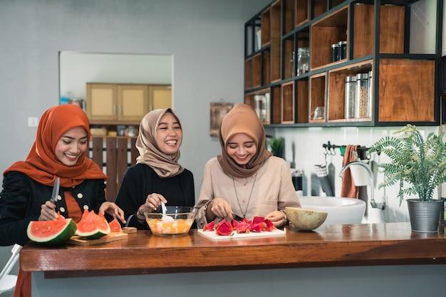 Молодая женщина в хиджабе готовит фрукты для приготовления коктейля