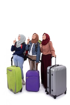 Young hijab woman standing holding suitcase, bag with hands pointing