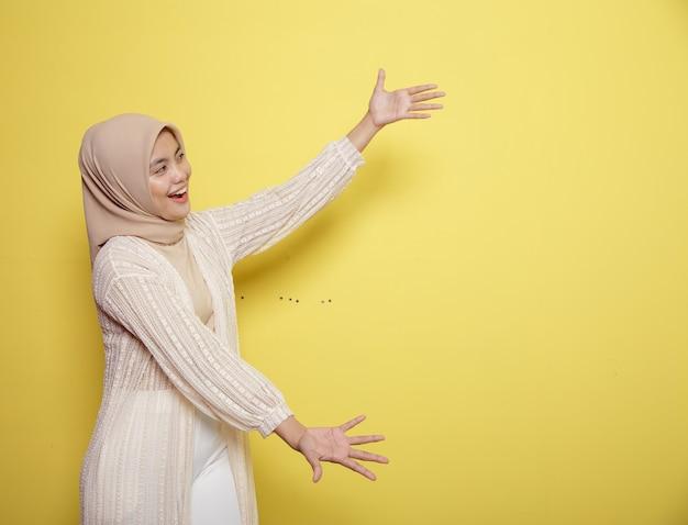 Молодые женщины в хиджабе счастливы и показывают пространство для копирования на желтом фоне