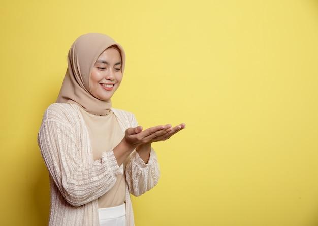 Молодые женщины в хиджабе счастливы шоу и, глядя на ее руку, копируют пространство на желтом фоне