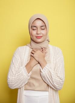 Молодые женщины в хиджабе улыбаются, просят безмолвные молитвы, держа сундук на желтом фоне