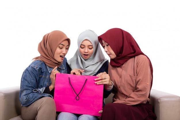 驚いた若いヒジャーブ女性が買い物袋を開く