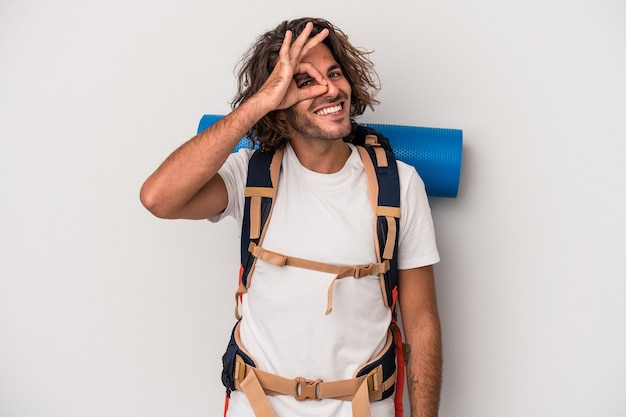 Young hiker caucasian man isolated on gray background excited keeping ok gesture on eye.