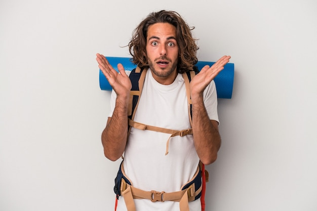Young hiker caucasian man isolated on gray background surprised and shocked.