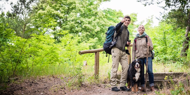 Young hiker couple with bernese mountain dog on forest trail