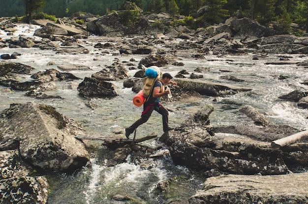산 강을 건너는 젊은 등산객. 멋진 산. 돌을 건너는 하이킹 강. 타지키스탄