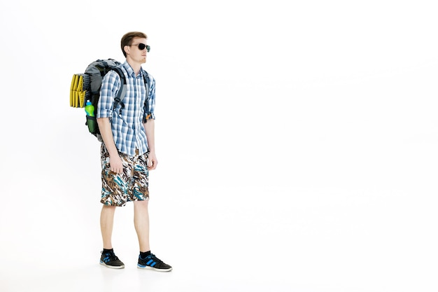 Молодой путешественник в солнцезащитных очках с рюкзаком на белом фоне