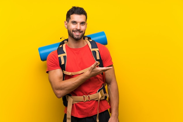 Young hiker man extending hands to the side for inviting to come