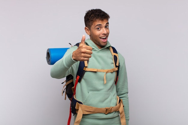 Young hiker man feeling proud, carefree, confident and happy, smiling positively with thumbs up