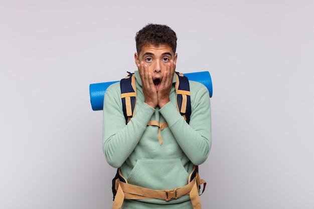 Молодой путешественник чувствует себя потрясенным и напуганным, выглядит испуганным с открытым ртом и руками по щекам