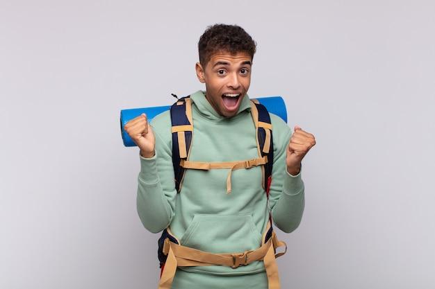 Молодой путешественник чувствует себя потрясенным, взволнованным и счастливым, смеется и празднует успех, говоря