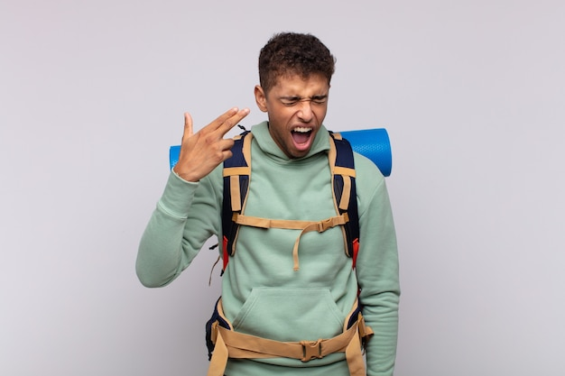 Young hiker man looking unhappy and stressed, suicide gesture making gun sign with hand